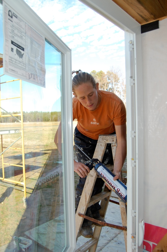 Megan caulking windows in our bedroom-to-be